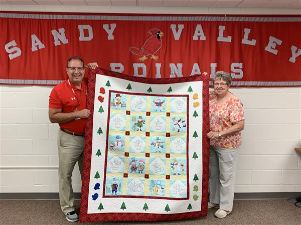 David Fischer and Kaye Pomesky holding the Snowman Quilt
